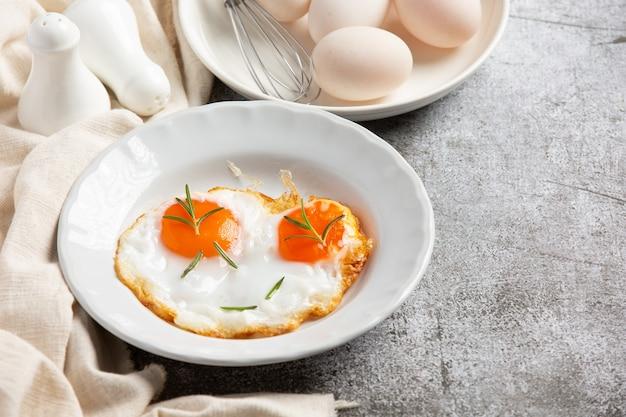 Жареные яйца в белой тарелке