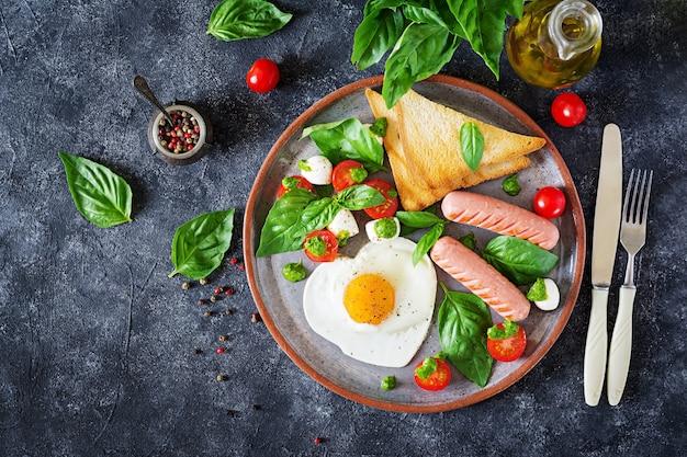 Жареные яйца в форме сердца, колбаса, тосты и салат с помидорами, базиликом и моцареллой.