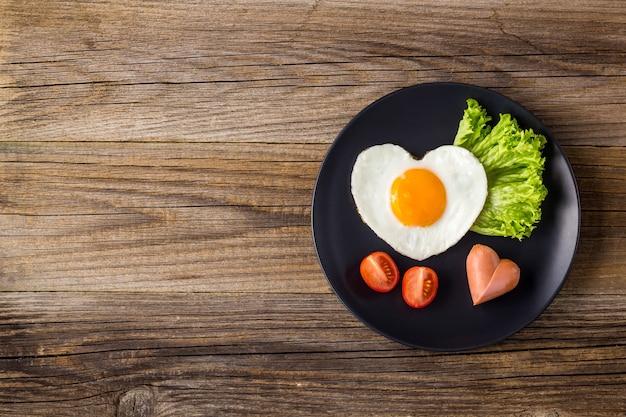 ソーセージ、ハーブ、トマトが入ったハート型の目玉焼き。白い背景の上のバレンタインデーにあなたの愛する人のための朝食。コピースペースのある上面図