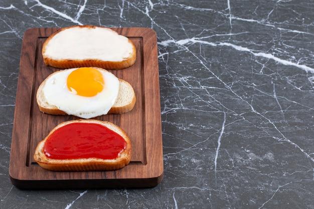 Жареные яйца, джем и сыр на индивидуально нарезанном хлебе на доске, на мраморной поверхности