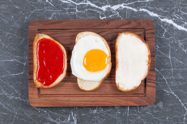 Fried eggs, jam and cheese on individually sliced bread on the board , on the marble surface