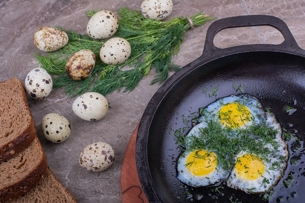 Uova fritte in padella metallica con erbe aromatiche.