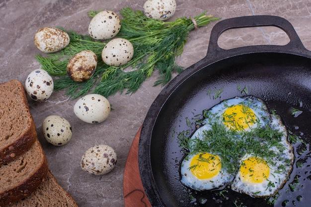 Uova fritte in una padella metallica con erbe aromatiche.