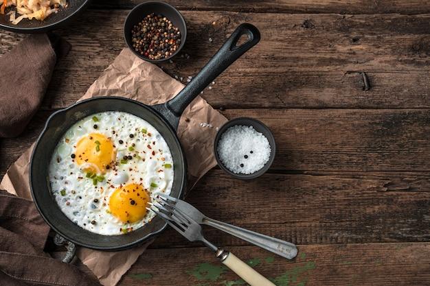 Жареные яйца на деревянных фоне. вид сверху, с местом для копирования. концепция приготовления пищи.
