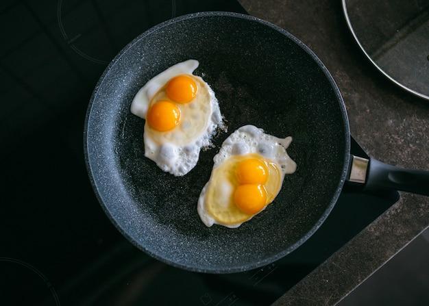 Жареные яйца на черной сковороде