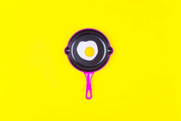 黄色の上のピンクのフライパンで目玉焼き