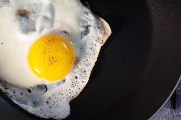 Fried eggs in a pan isolated on a black  close-up. view from above.