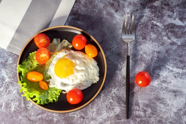Fried eggs in a pan with cherry tomatoes and coffee for breakfast