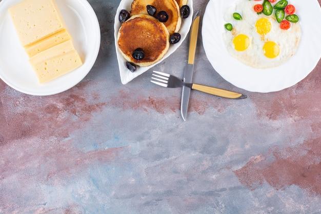 大理石のテーブルに目玉焼き、パンケーキ、黄色いチーズ。