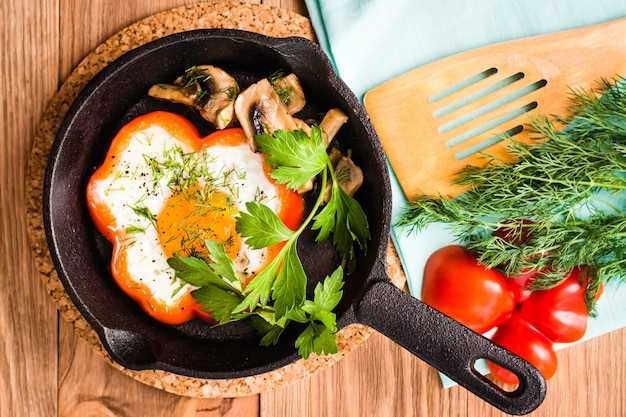 Fried eggs in pepper, herbs and mushrooms in the iron pan