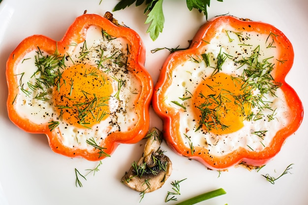 Fried eggs in pepper and herbs on the plate