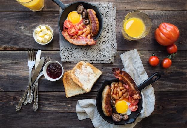 Яичница, сосиски, бекон, бобы и грибы в железной сковороде на деревенском деревянном фоне