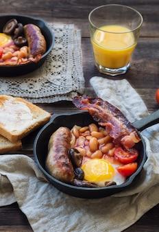 素朴な木製の背景に目玉焼き、ソーセージ、ベーコン、豆、キノコの鉄フライパン、トースト、オレンジジュース、バター、ジャム。フルイングリッシュブレックファスト。セレクティブフォーカス。