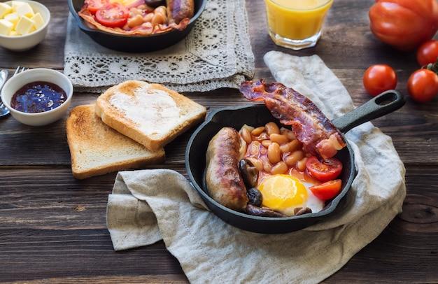 Жареные яйца, сосиски, бекон, фасоль и грибы в сковороде железа, тосты, апельсиновый сок, масло и джем на деревенском деревянном фоне. полный английский завтрак.