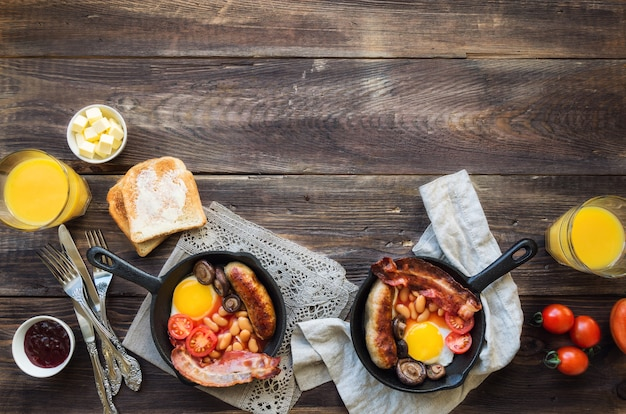 Fried eggs sausages bacon beans and mushrooms in iron skillet on rustic wooden background
