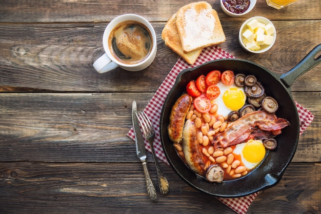 Fried eggs, sausages, bacon, beans and mushrooms in iron skillet, toasts, coffee, butter and jam on rustic wooden background. full english breakfast. top view.
