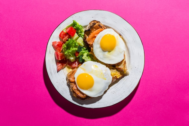 Fried eggs on toasts with vegetables on a pink surface