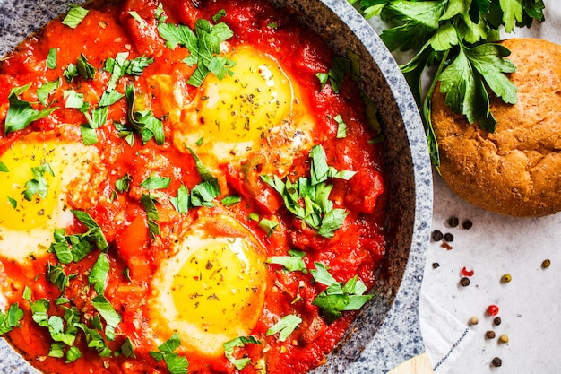 Fried eggs in tomato sauce with herbs