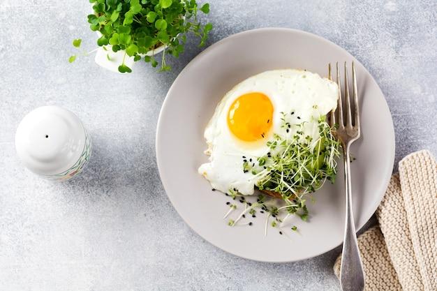 회색 콘크리트 오래 된 배경에 회색 세라믹 접시에 arugula microgreen와 튀긴 계란. 전통적인 영국식 아침 식사. 평면도