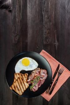 ベーコンと野菜の目玉焼き、木の素朴なボードでの朝食