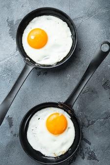 Жареные яйца с беконом и овощами в чугунной сковороде на сером фоне