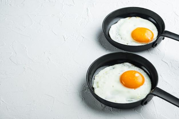 베이컨과 야채와 함께 튀긴 계란, 흰색 배경에 주철 프라이팬에 설정, 텍스트 copyspace위한 공간