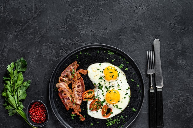 Fried eggs with bacon. black background. top view. space for text