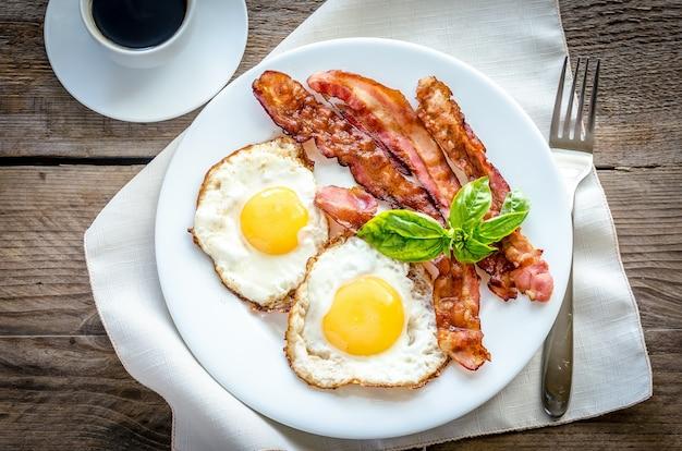 Жареные яйца с беконом на деревянном столе
