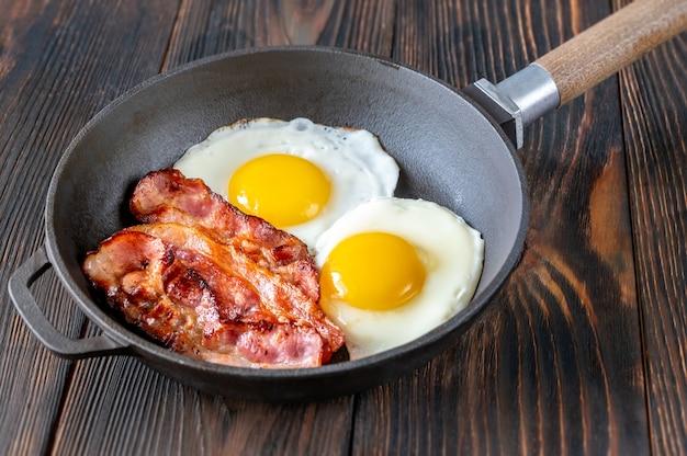 Жареные яйца с ломтиками бекона на сковороде