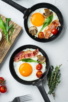 Fried eggs with bacon and vegetables set in pan