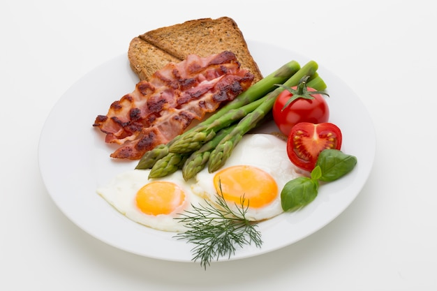 Fried eggs with bacon on the wooden table. Premium Photo