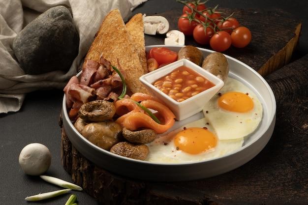 Яичница с фасолью в томатном соусе, жареные грибы, бекон, лосось, куриные колбаски, помидоры черри и тосты. сытный завтрак