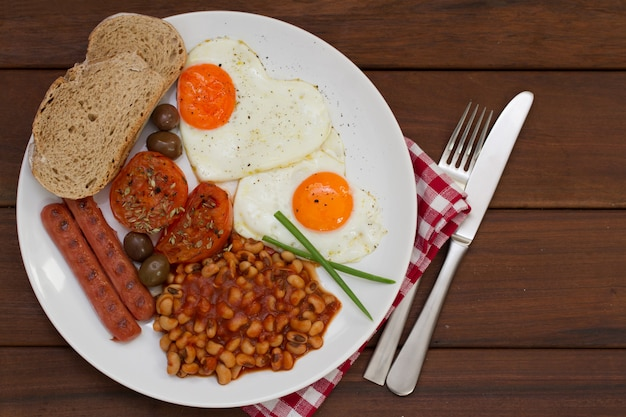 Fried eggs with bread, sausages and beans on white plate