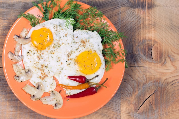 Fried eggs with champignons, dill and red chili pepper