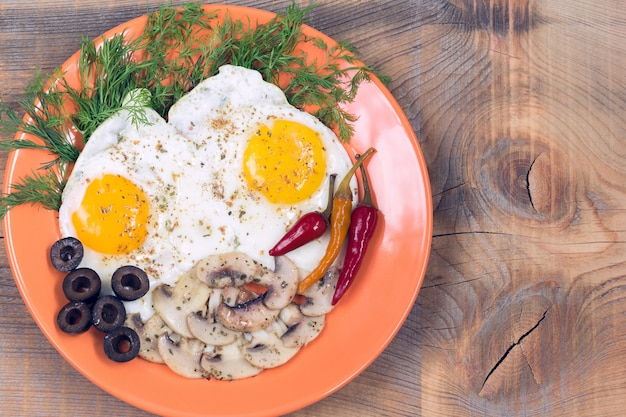 Fried eggs with champignons, olives, dill and red chili pepper