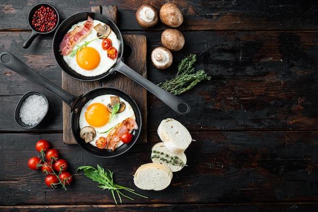 체리 tomatoe와 오래 된 어두운 나무 테이블 배경에 주철 프라이팬에서 아침 식사를 위해 빵과 튀긴 계란, 평면도 평면 누워, 텍스트 copyspace를위한 공간
