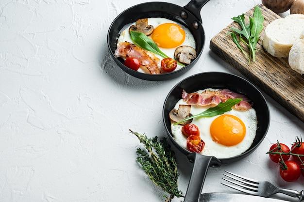 체리 tomatoe와 빵과 함께 튀긴 계란, 흰색 배경에 주철 프라이팬에서 아침 식사, 텍스트 copyspace위한 공간