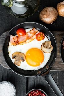 Жареные яйца с помидорами черри и хлебом на завтрак в чугунной сковороде на фоне черного деревянного стола, плоская планировка, вид сверху