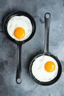 Жареные яйца с помидорами черри и хлебом на завтрак в чугунной сковороде, на сером фоне, вид сверху плоская планировка