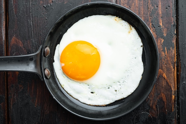 Жареные яйца с помидорами черри и хлебом на завтрак на чугунной сковороде, на фоне старого темного деревянного стола, вид сверху плоская планировка