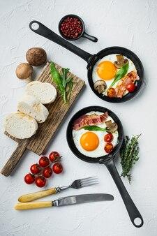 Яичница с помидорами черри и хлебом на завтрак на чугунной сковороде, на белом фоне, вид сверху плоская