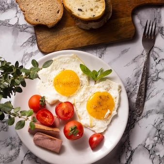 Fried eggs with cherry tomatoes and hotdogs