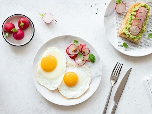 Fried eggs with fresh radish salad and toast with mashed avocado. healthy food concept