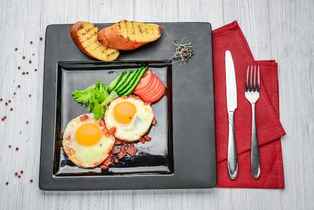 木製のテーブルに新鮮な野菜とベーコンと目玉焼き