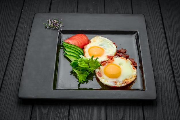 Fried eggs with fresh vegetables and bacon on the wooden table