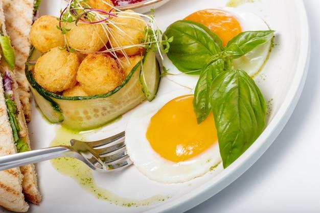 Яичница с жареными картофельными шариками на белом фоне
