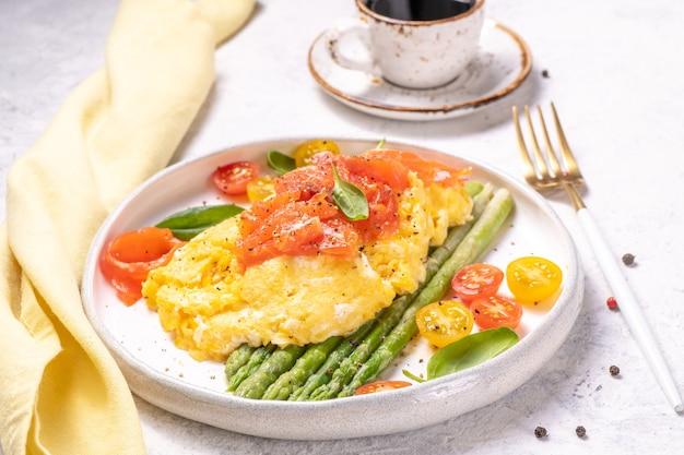Яичница с зеленой спаржей и лососем, помидорами черри и свежим шпинатом.