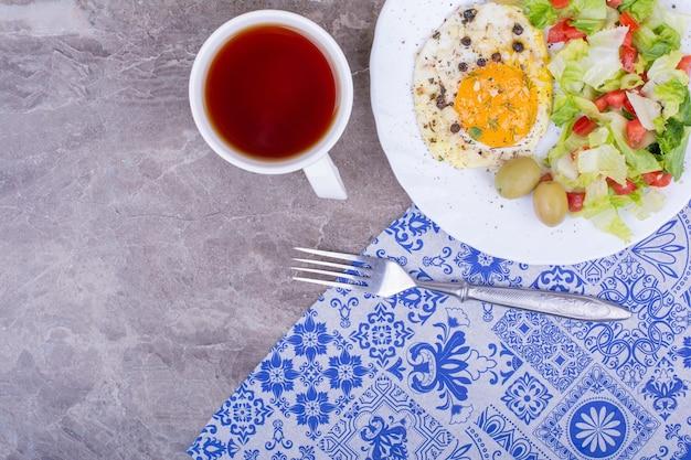Uova fritte con insalata verde e una tazza di tè.
