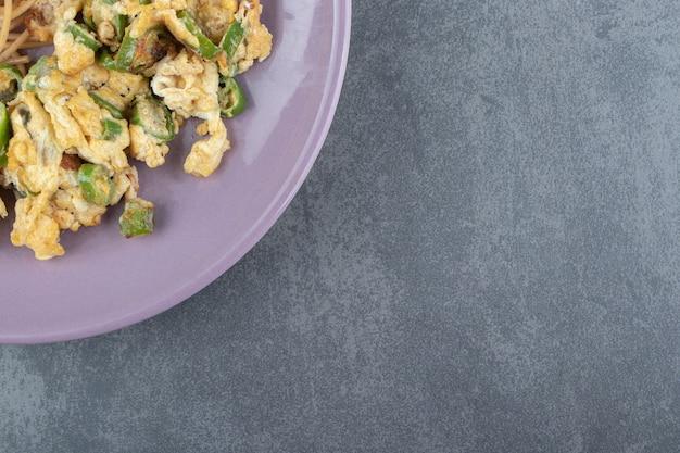 Uova fritte con verdure sul piatto viola.