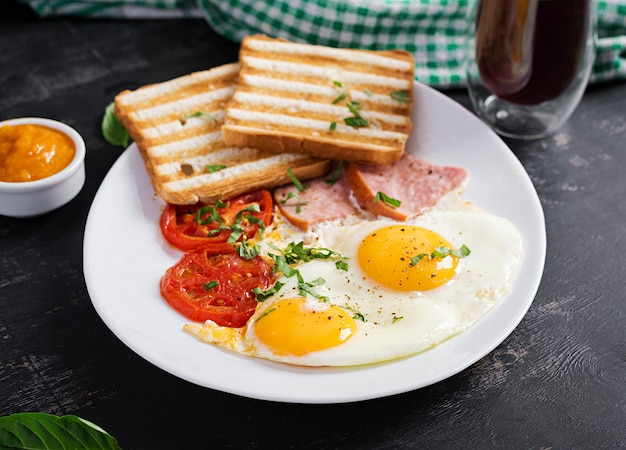 Fried eggs with ham, tomatoes and toasts. delicious english breakfast. brunch.